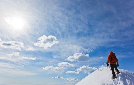 Mountaineer reaching the top of a snowcapped mountain peak. Horizontal frame. Standard-Bild