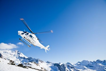 Heli Skiing Helicopter is landing on a ski slope in Gressoney Ski Resort, Aosta, Italy.