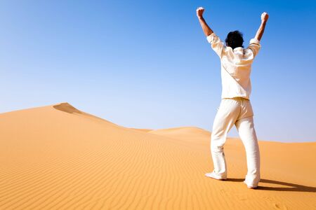 chebbi: Rear view of a adult white man standing on a sand dune and holding arms up. Erg Chebbi, Maroc