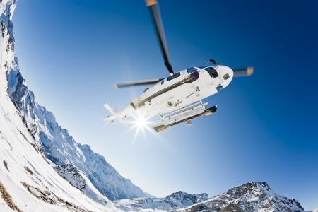 aosta: Heli Skiing Helicopter is landing on a ski slope in Gressoney Ski Resort, Aosta, Italy.