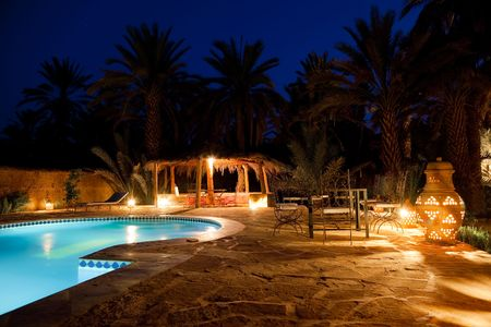 chair garden: Pool and garden of a maroccan kasbah hotel at night, Maroc, Africa. Stock Photo