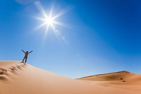 erg: Success concept: rear view of a adult white man standing on a sand dune and holding arms up. Erg Chebbi, Maroc
