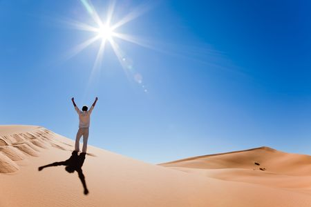 Success concept: rear view of a adult white man standing on a sand dune and holding arms up. Erg Chebbi, Maroc
