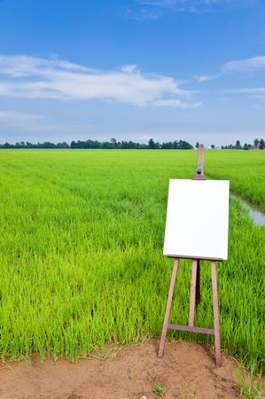 Blank canvas on a wooden easel over a green field. Large copy space on the white canvas. Vertical orientation photo