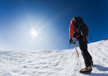 ice climbing: Mountaineer reaching the top of a snowcapped mountain peak. Horizontal frame. Stock Photo