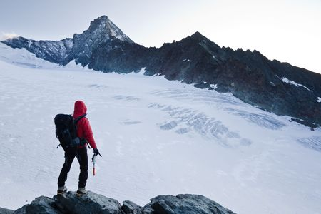 Climber stands in front the glacier and the peak of Mt Grivola, Gran Paradiso National Park, Italy. Stock Photo