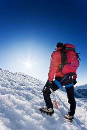 summit: A lone mountaineer reaches the top of a high mountain peak. Monte Rosa, Swiss.
