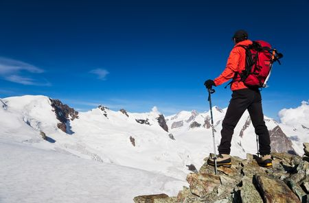conquering: Male hiker standing in front of Monte Rosa Glacier during an high altitude hiking. Switzerland, Europe.