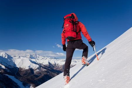snowed: A male climber , dressed in red, climbs down a snowy slope. Winter clear sky day. In background the Monte Rosa massif, Italy, Europe.