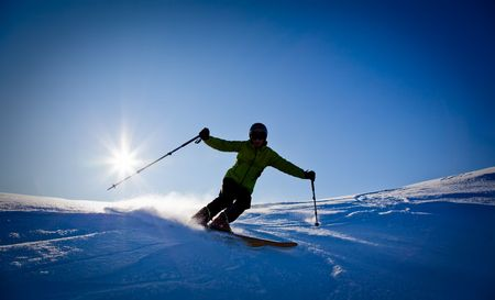 Young male freerider skier moving down in snow powder at sunset; italian alps. photo