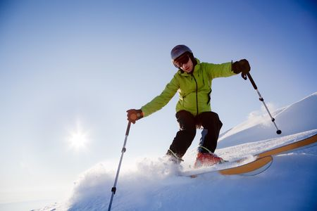 Young male freerider skier moving down in snow powder at sunset; italian alps. Standard-Bild