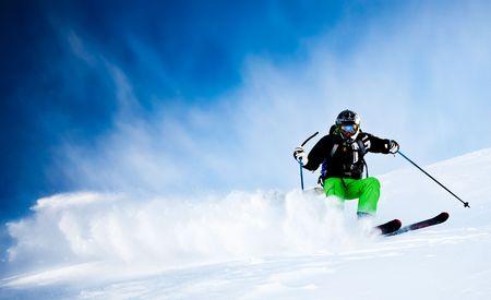 ski slopes: Freeride maschio giovane sciatore oltre il cielo blu, trasformando in neve fresca; giacca nera; Pantalone verde; orientamento orizzontale