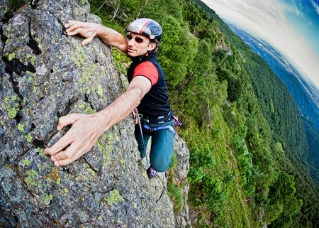 to climb: Young white man climbing a steep wall in mountain, rock-climb extreme sport, summer season. Horizontal orientation