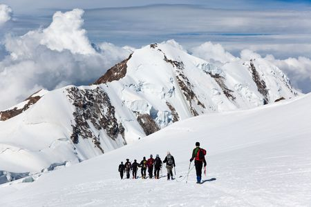 A large group of mountaneers walking on a glacier in a sunny day: in background the snowed peaks of Lyskamm (4550 mt) , Monte Rosa range, West Alps, Switzerland, Europe. photo