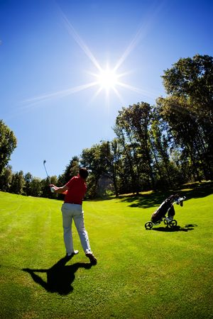 One young white male golfer, red shirt and white pants, goes for the green on the fairway. Vertical frame, clear summer day, back-light. Standard-Bild