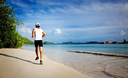 man rear view: One young man running on a tropical empty beach at sunrise, rear view ; Seychelles, Indian ocean