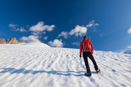 mont: A male mountaineer walking uphill on a glacier. Mont Blanc, France. Stock Photo