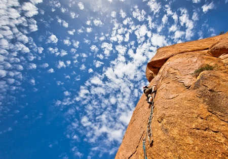 alpinist: rock climbing:young climber on a steep granitic mountain over a blue sky