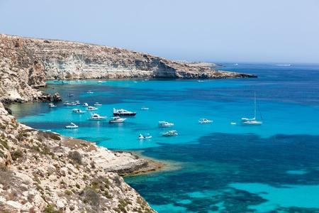 Lampedusa island, Mediterranean Sea, Italy: boats anchored in port behind island Standard-Bild