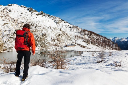 One man young male hiker stands in front of a alpine lake looking to the snowy landscape, rear view. photo