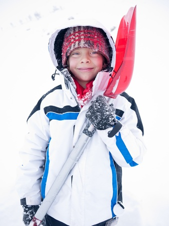 A smiling caucasian child looking at camera, wearing white winter clothing and holding a red snow shovel. Winter season. photo