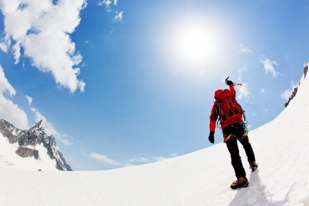 A male mountaineer expresses his joy reaching the summit of a snowed mountain peak. Mont Blanc, Chamonix, France. photo