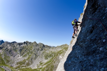 Caucasian male climber climbing a steep wall  In background a summer alpine landscape  Clear sky, day light  West italian Alps, Europe