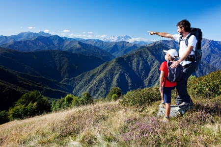 family vacation: Man and young boy standing in a mountain meadow. The man points to a direction, showing something to the boy. Summer season, clear blue sky. In background the Monte Rosa Massif, Piemonte, west italian Alps. Stock Photo