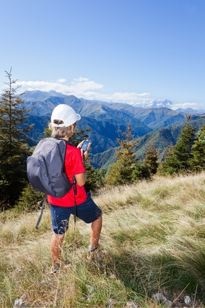 Young boy standing along a mountain path using a  smartphone for checking his gps position. Summer season, clear blue sky. Boy is wearing a red shirt, white cap and a grey backpack. Place of shooting: Valle Sessera, Piemonte, west italian Alps. photo