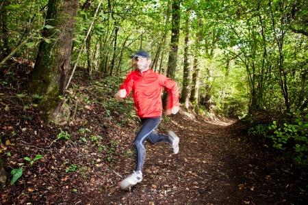 szlak: Mężczyzna biegacz biegania w lesie na szlaku. Czerwona koszula i czarne spodnie. Sezon letni. Lekkie rozmycie obrazu w biegacza aby pokazać ruch. Poziomy kompozycja.