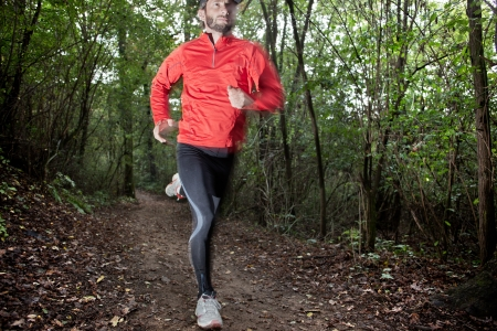 running pants: Male trail runner running in the forest on a trail. Red shirt and black pants. Summer season. Slight blur in runner to show motion. Horizontal composition.
