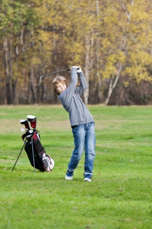 boy alone: Young golfer playing a shot from the fairway  Blonde caucasian kid  Autumn Season