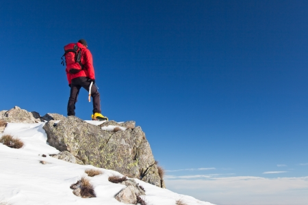 Male trekker standing on a rock while observing the horizon  Clear blue sky in background
