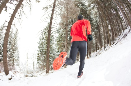men running: Winter trail running  man takes a run on a snowy mountain path in a pine woods  Stock Photo