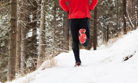 Winter trail running  man takes a run on a snowy mountain path in a pine woods  Stock Photo