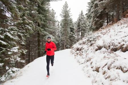 uomo rosso: Trail running invernale uomo prende una corsa su un percorso di montagna di neve in un bosco di pini Archivio Fotografico