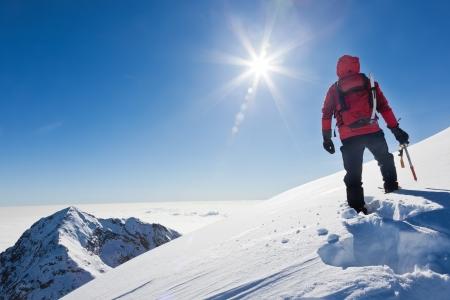 mountain climber: Alpinista raggiunge la cima di una montagna innevata in una soleggiata giornata invernale Alpi Occidentali, Biella, Italia