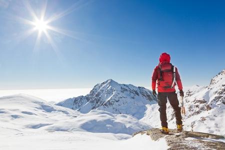 登る: クライマーは晴れた冬の日西アルプス ビエッラ、イタリアで雪に覆われた山の風景を見ています。 写真素材