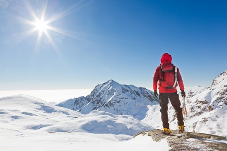 Climber looking at a snowy mountain landscape in a sunny winter day   Western Alps, Biella, Italy  photo