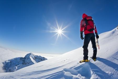 stijger: Bergbeklimmer bereikt de top van een besneeuwde berg in een zonnige winterse dag westelijke Alpen, Biella, Italië