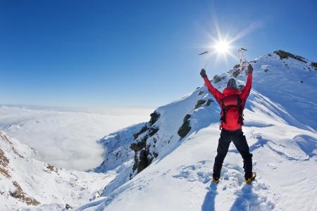 klimmer: Bergbeklimmer bereikt de top van een besneeuwde berg in een zonnige winterse dag