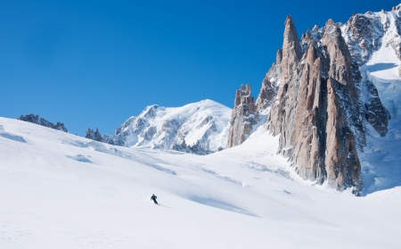 Skier goes downhill on a alpine glacier  In background the amazing panorama of the Mont Blanc peaks Vallée Blanche, Chamonix, France