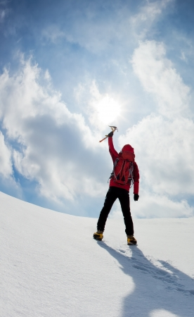 ice axe: Mountaineer walking uphill along a snowy slope  Rear view  Western Alps, Europe