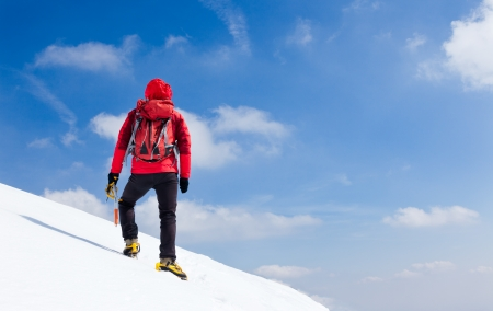 alpinist: Mountaineer walking uphill along a snowy slope  Rear view  Western Alps, Europe