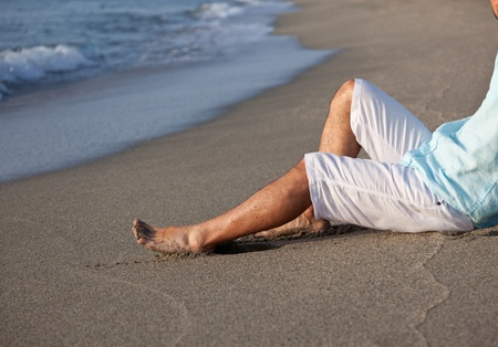 Caucasian young man, in casual clothing, sitting on beach in the sunrise light  photo