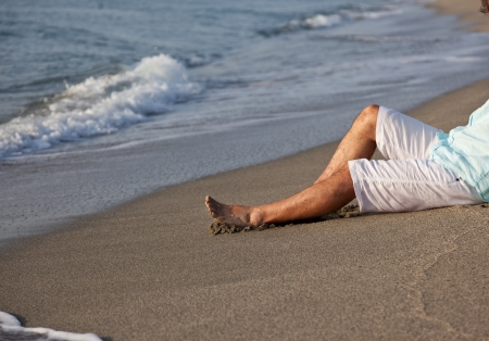 wetting: Caucasian young man, in casual clothing, sitting on beach in the sunrise light