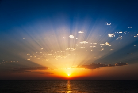 Perfect sunrise on the sea, with radiant rays of sun over a warm colourful horizont  Standard-Bild