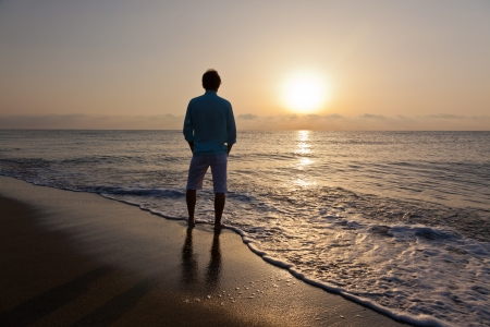 man rear view: Alone caucasian man standing on beach watching the sunrise  Stock Photo