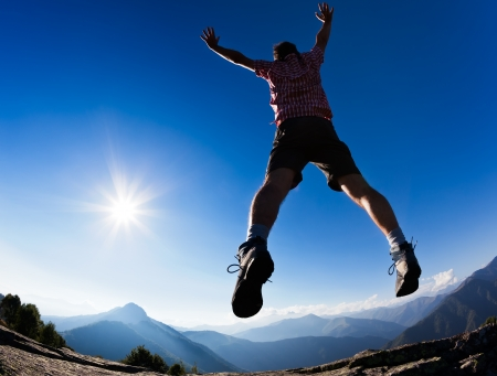 freedom fun: Man jumping in the sunshine against blue sky  Concept  freedom, success, energy, vitality  Stock Photo