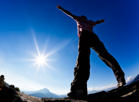verve: Man opens his arms in the sunshine against blue sky. Concept: freedom, success, energy, vitality.